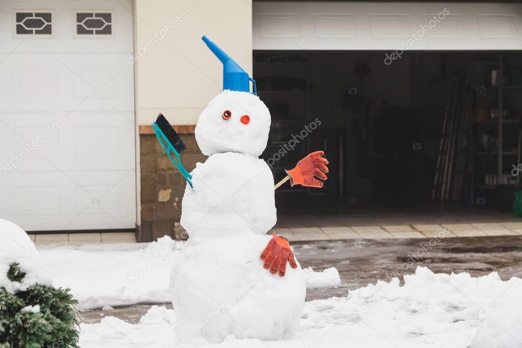 Snowman motorist stands in front of the garage. For decoration use a watering can, a brush and working glove
