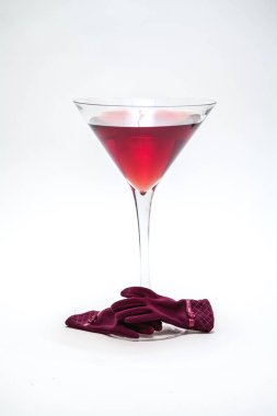 Invisible with a glass. A huge glass goblet with red wine on a white background. Near red women's glove