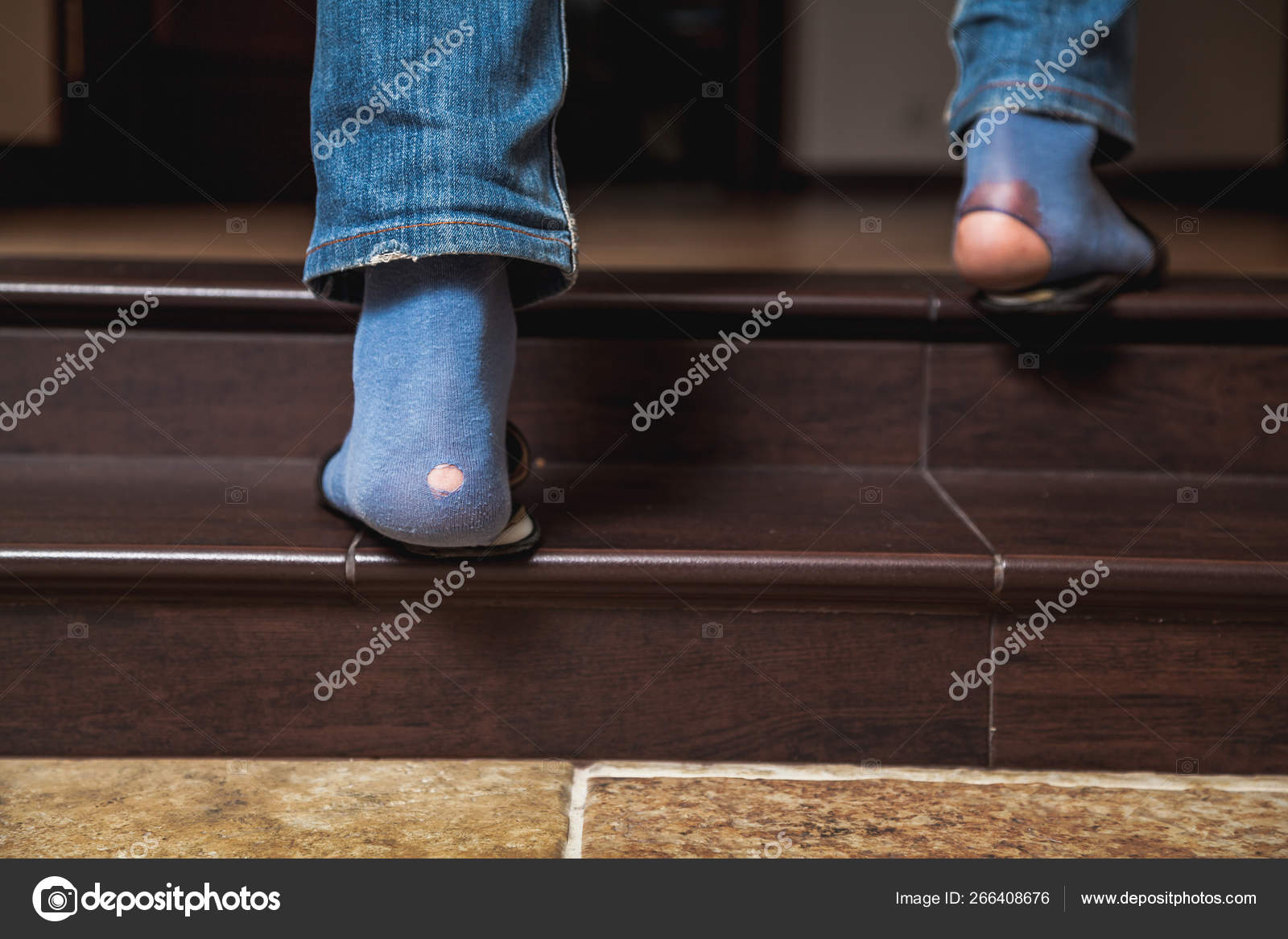 Feet In Jeans And Holey Socks Go Up Stairs Stock Photo