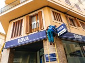Worker cleaning the facade of the Spanish BBVA