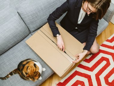 Woman unboxing unpacking cardboard box with her cat