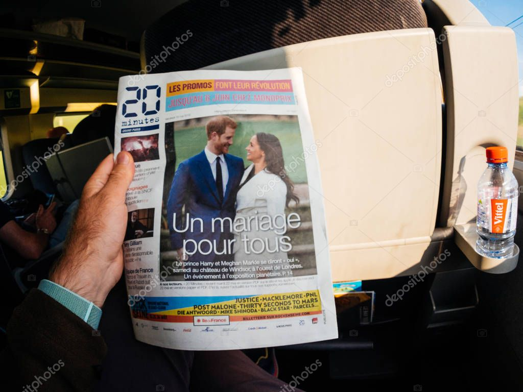 FRANCE - MAY 20, 2018: Man reading in first class of a TGV SNCF train the cover newspaper of 20 minutes featuring portraits of Prince Harry and Meghan Markle lifestyle event