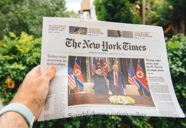 Man reading in city newapsper Kim-Trump meeting