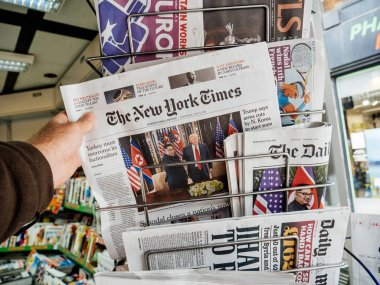 Man buying The New York Times newspaper at press kiosk