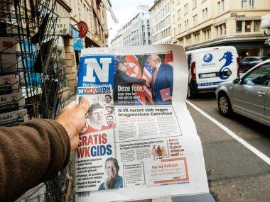 PARIS, FRANCE - JUNE 13, 2018: Man buying Het Nieuwsblad newspaper at press kiosk showing on cover U.S. President Donald Trump meeting North Korean leader Kim Jong-un in Singapore