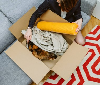 Business woman unpacking unboxing cardboard box box containing y