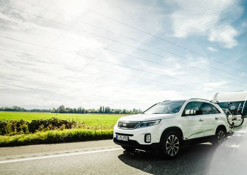 MUNCHEN, GERMANY - OCT 7, 2018: Fast driving on German autobahn Kia Niro Hybride Rechargeable car with RV recreational vehicle trailer - beautiful sunlight flare