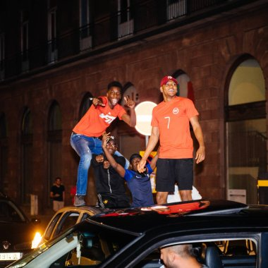 STRASBOURG, FRANCE - JULY 10, 2018: Arab boys dancing on cars happiness celebration after the victory of France qualify for the final of the 2018 FIFA World Cup after their victory