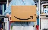 Paříž, Francie – 4. července 2018: Žena přijímá Amazon Prime balík doručen chystá udělat unboxing, hrdý Amazon Prime klienta s knihovnou v pozadí