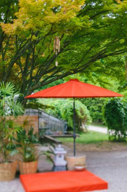 Japanese wind chimes wooden bamboo bells handed on tree in Japanese garden with red umbrella and potteries - tilt-shift lens focus effect