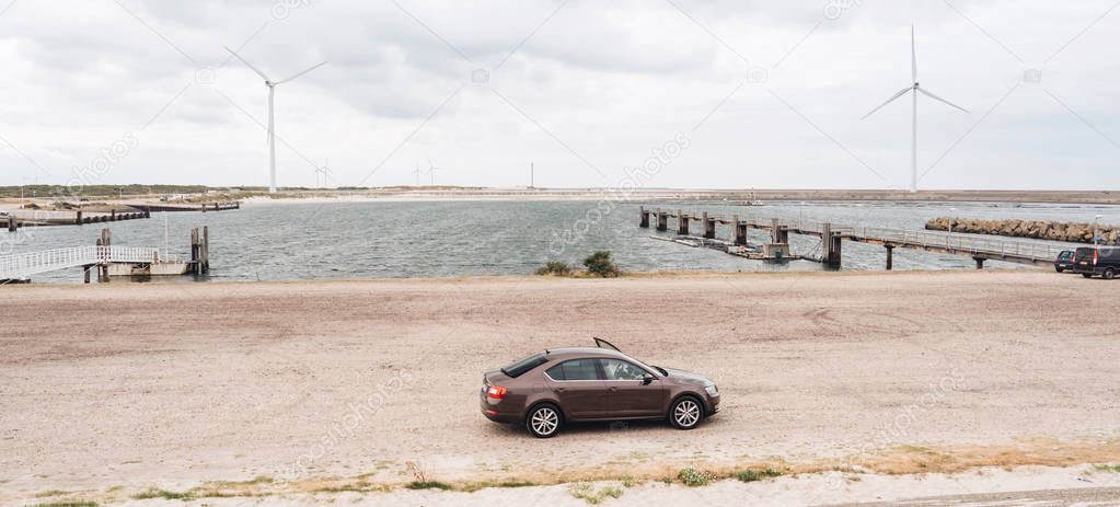 Vrouwenpolder, Netherlands - Aug 25, 2018: Luxury Skoda car parked in the bay - elevated view - rainy cloudy netherlands weather and big wind turbines for the elctric hybrid car