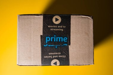Amazon Prime cardboard box delivery yellow background