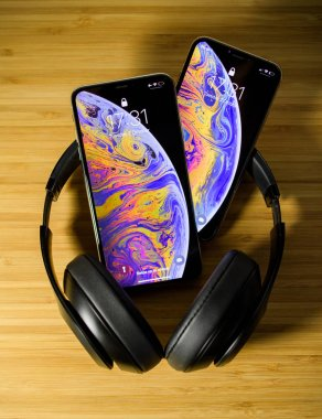 PARIS, FRANCE - OCT 2, 2018: comparing the new latest iPhone Xs and Xs Max smartphones telephones after the unboxing with Beats Studio 3 professional headphones