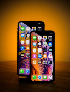 PARIS, FRANCE - OCT 2, 2018: Two smartphones from Apple Computers - iPhone Xs and Xs Max with orange light in the background - spot studio show