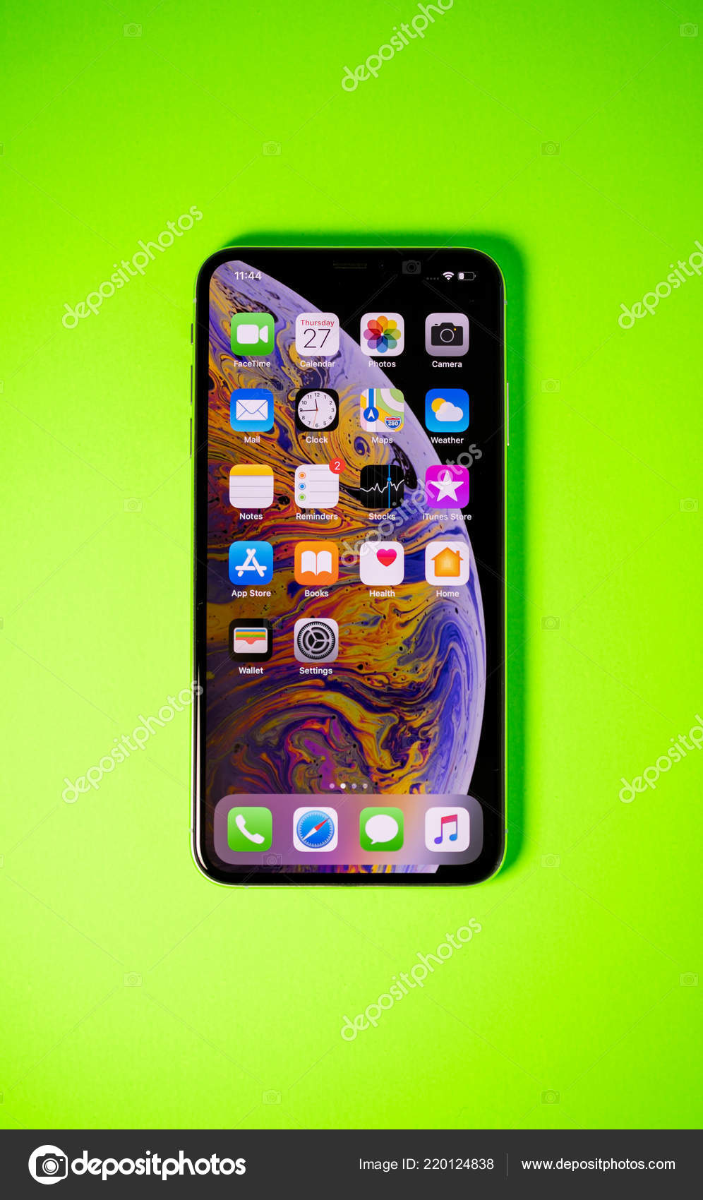 Apple Iphone Xs Max Against Vibrant Green Background Stock