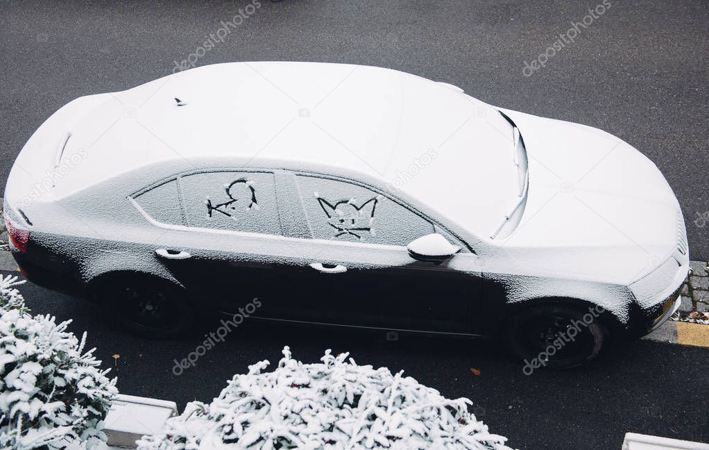 Car covered with snow with cat am mouse silhouettes