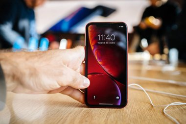 PARIS, FRANCE - OCT 26, 2018: male hand holding on wooden table latest red iPhone XR smartphone in Apple Store Computers during the launch day - customers in background