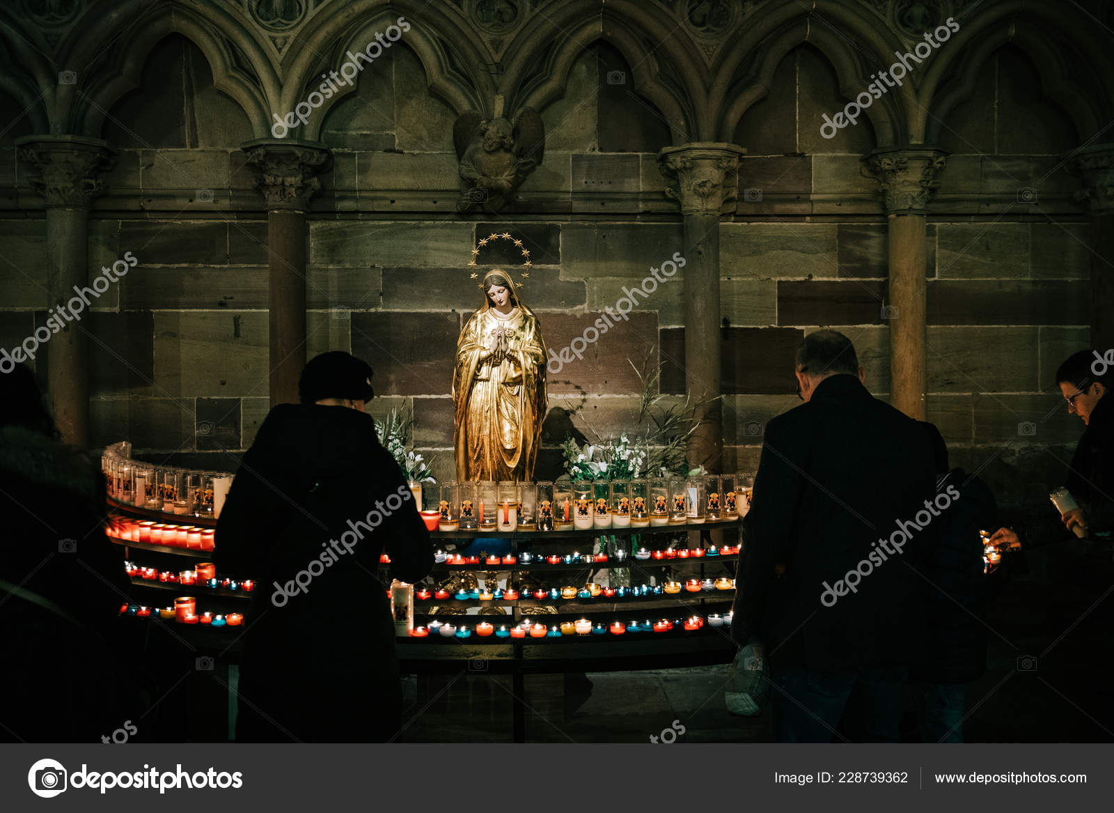 Man and woman light candles in Cathedral Notre-Dame with