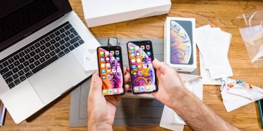 Paris, France - Sep 21, 2018: Apple fan boy unboxing latest new Apple Iphone Xs Max and Xs flagship smartphone mobile manufactured by Apple Computers watching the OLED display screen stock vector