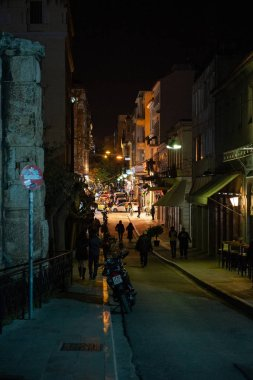 Pedestrians walking on the dark street in central Athens