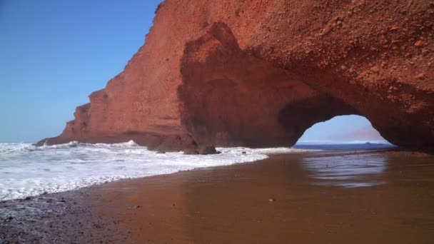 Flying through the arch on Legzira beach with arched rocks on the Atlantic coast in Morocco