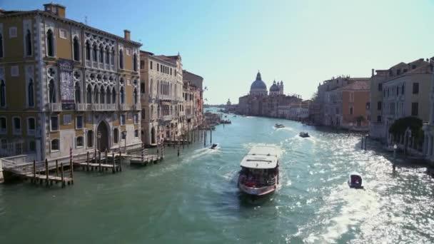 Lodě plují na jednom z mnoha zpátečních kanálů v Benátkách Itálie jako turisté potulují úzkými ulicemi