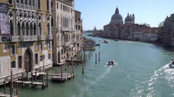 Hajók lebegnek a sok hátsó csatorna egyikén Velencében Olaszországban, miközben turisták kóborolnak a szűk utcákon.