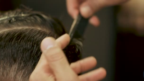 Hand haircutter combing wet hair and using hairdressing scissors for cutting close up