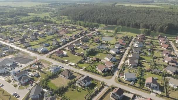 Letecké záběry z nadzemních evropských nemovitostí, domů shora. Letecká střela přes horní část obytných nemovitostí. Letecký pohled na vesnici. Video bez korekce barev 4k