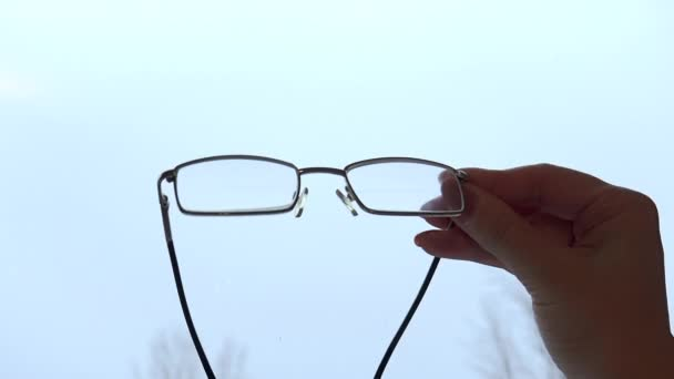 Brýle v držení rukou na bílém pozadí, izolované