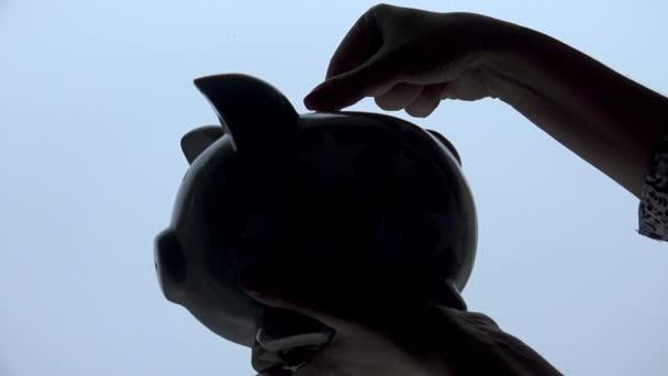 Ruka, uvedení mincí v prasátko, izolované, silueta