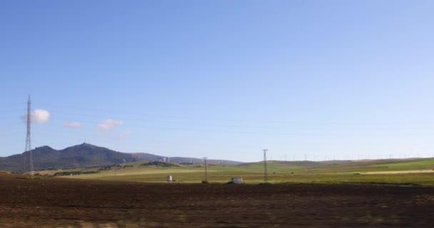 Záběr z vozu: krajina s Větrná obnovitelné energie turbíny, příroda rostliny, signály a půdy pohybuje jako pozadí. Cadiz, Andalusie, Španělsko, Evropa