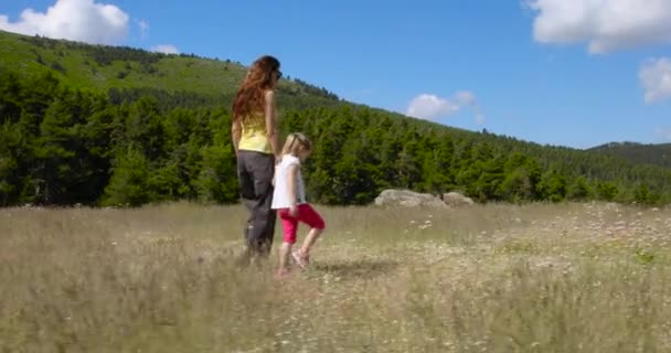 Woman holding hand and talking to her daughter, four years old blonde girl, walking in meadow, in Guadarrama mountains, near Madrid, Spain, Europe. 4k video.