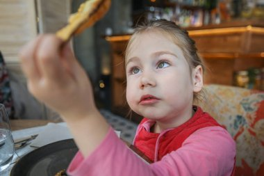 portrait of four years old blonde girl eating and looking at a fried eggplant slice in her hand, sitting in restaurant