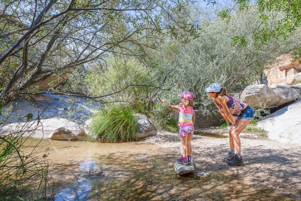 adventurous family: five years old girl pointing with magnifying glass next to her mother, with caps, discovering nature in a river of Camorza Gorge (Madrid, Spain, Europe)