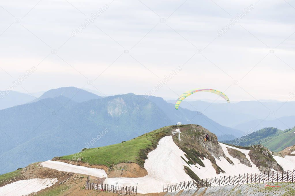 RUSSIA, SOCHI - MAY 25, 2018: Editorial photo on top of rose Peak, Rosa Khutor. Two people flying a paraglider. Outdoor activity