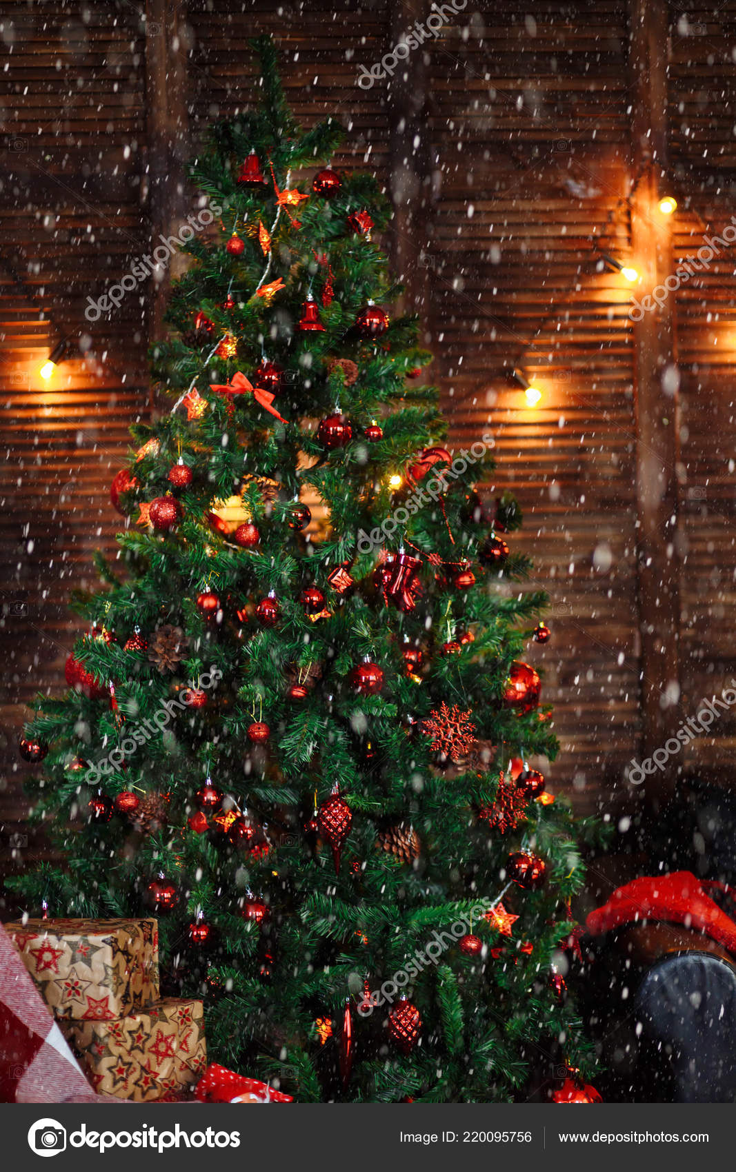 Green Christmas tree decorated with red toys ornaments pine cones beads garlands box sofa wooden wall floor in the dark