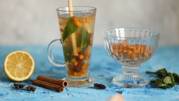 Színes forró homoktövis tea fahéjas botokkal, csillagánizs és friss homoktövis bogyókat a kék rusztikus tábla.