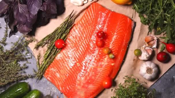 auf dem Gemüse und rotem Fisch auf dem Tisch fallen Gewürze und kleine Kirschtomaten, Draufsicht. Nahaufnahme