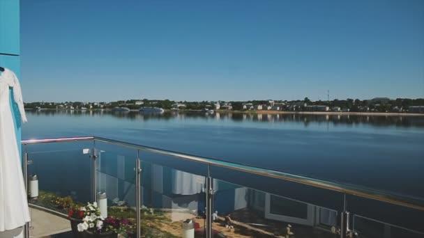 Svatební šaty na balkon, na břehu řeky a modrá obloha