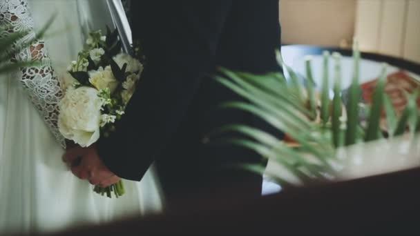 Milující pár se drží v rukou svatební kytice