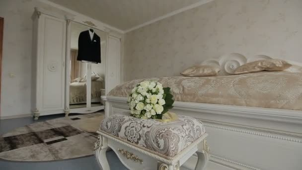 Una chaqueta. El traje del traje se cuelga en la percha en el cuarto. Ver a  través del espejo en que se encuentra un ramo de flores y anillos
