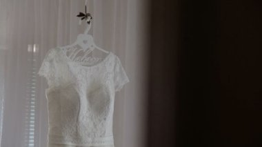1822683af0 Luxury wedding dress hanging in bedroom. Silhouette of amazing ...