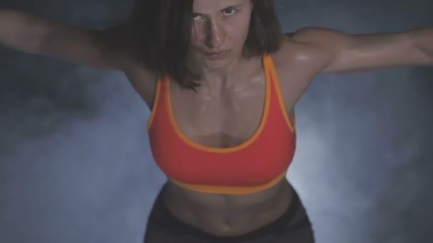 Donna bella palestra con sollevamento manubri. Ragazza sportiva mostrando il suo corpo ben addestrato. Muscoli ben sviluppati di allenamento della forza.