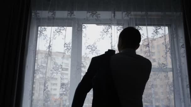 Silueta de un hombre poniendo su chaqueta en cuarto oscuro — Vídeos ...