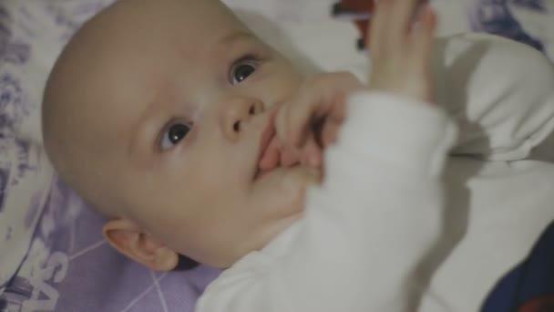 Happy newborn baby yawns closeup in white bed