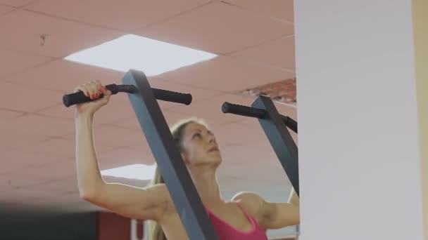 Fitness-Coach des Sportvereins macht Klimmzüge auf dem Simulator zur ...
