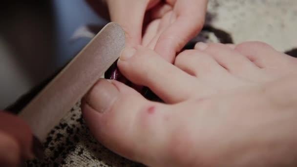 Péče o dívce nohy pedikúra, polské, krásná světla. Nechte se hýčkat v salonu. Master se stará o nehty a nohy klienta, dělá pedikúru. Peeling nohou pedikúra postup