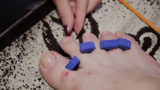 Pflege der Mädchenbeine Pediküre, Politur, schöne Lichter. Pediküre im Salon. Der Meister pflegt die Nägel und Füße des Kunden und führt die Pediküre durch. Peeling Füße Pediküre Verfahren