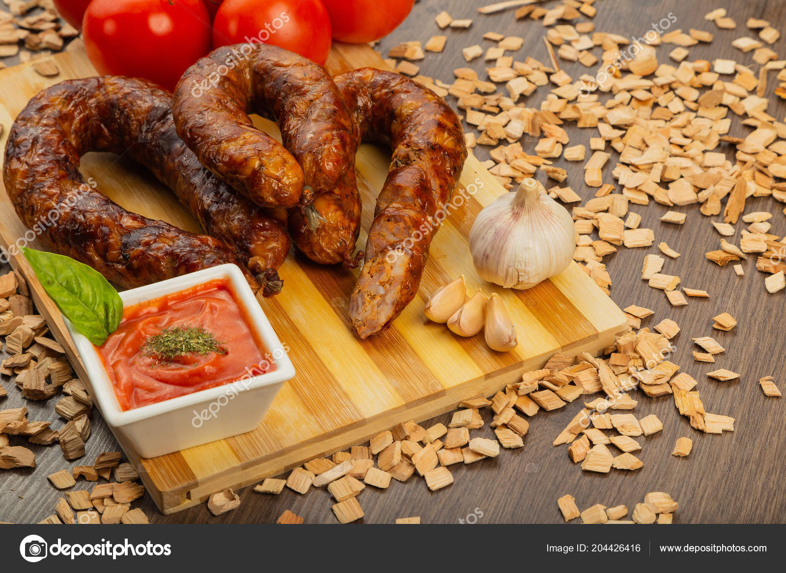 Homemade sausage on a wooden background with seasonings and sauce. — Stock Photo